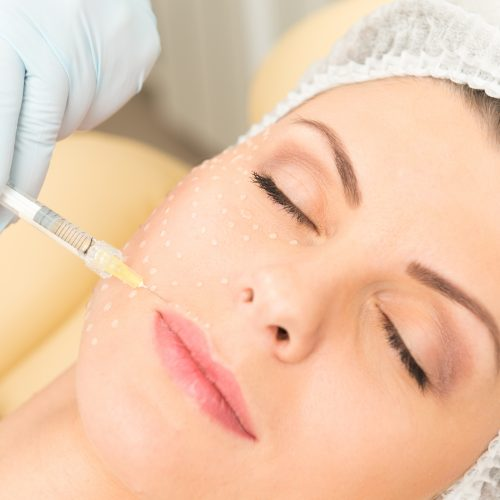 Cosmetic injection to the pretty caucasian woman face and beautician hands with syringe